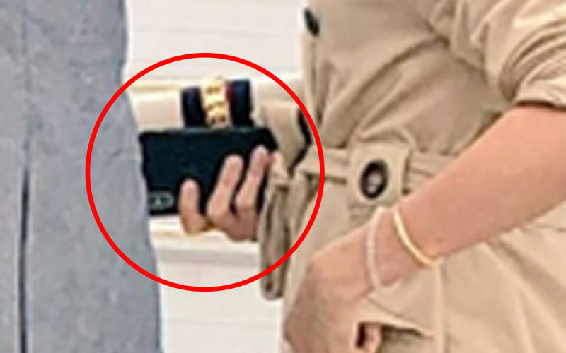 The Duchess of Sussex Meghan Markle can be seen clutching an iPhone as she prepares to leave Melbourne Airport on Thursday.