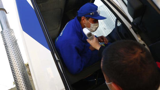 Yamil Peralta diperiksa suhunya di pintu masuk perusahaan tempatnya bekerja di Pilar, Buenos Aires, 28 Juli 2020. Di tengah lockdown, petinju profesional ini membuat alat olahraga darurat di rumahnya untuk berlatih dengan harapan lolos kualifikasi Olimpiade Tokyo 2021. (AP Photo/Marcos Brindicci)