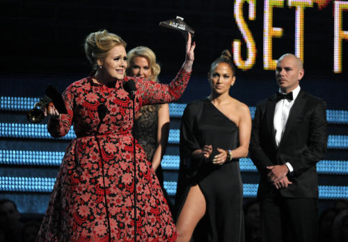 "Adele, left, accepts the award for best pop solo performance for ""Set Fire to the Rain"" at the 55th annual Grammy Awards on Sunday, Feb. 10, 2013, in Los Angeles. Looking on from right are presenters Pitbull and Jennifer Lopez. (Photo by John Shearer/Invision/AP)"