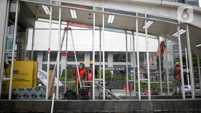 Pekerja menyelesaikan perbaikan Halte Transjakarta yang dibakar pasca aksi unjuk rasa di kawasan Bundara HI, Jakarta, Minggu (11/10/2020). Direktur Utama PT Transportasi Jakarta Sardjono Jhony Tjitrokusumo mengatakan, setidaknya ada 46 halte bus rusak. (Liputan6.com/Faizal Fanani)