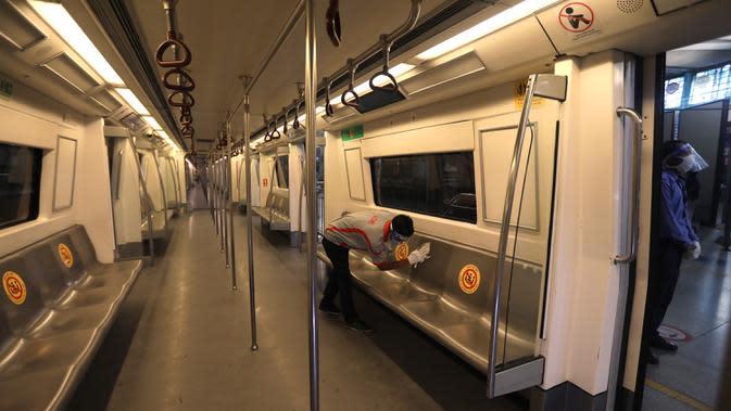 Seorang pekerja membersihkan interior gerbong metro di New Delhi, Kamis (3/9/2020). Jaringan Delhi Metro bersiap untuk melanjutkan layanan secara bertahap mulai 7 September setelah lebih dari 5 bulan ditutup karena pandemi virus corona Covid-19. (AP Photo/Manish Swarup)