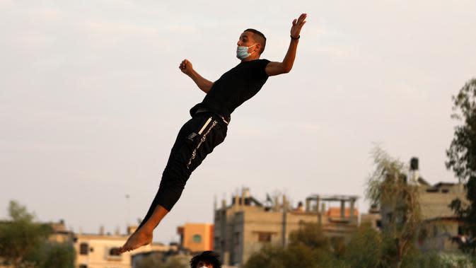 Seorang pemuda Palestina berlatih parkour selama pemberlakuan karantina wilayah (lockdown) di tengah wabah COVID-19, di Kota Khan Younis, Jalur Gaza selatan (18/9/2020). (Xinhua/Yasser Qudih)