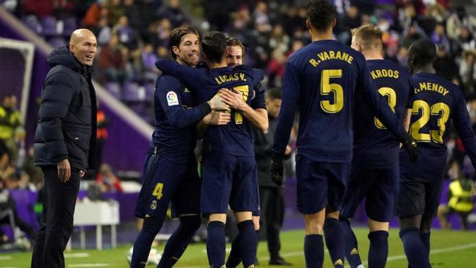 Pelatih Real Madrid, Zinedine Zidane (kiri), merayakan gol Nacho ke gawang Real Valladolid pada pertandingan pekan ke-21 La Liga Spanyol, di Estadio Jose Zorrilla, Minggu (26/1/2020). (AFP/Cesar Manso)