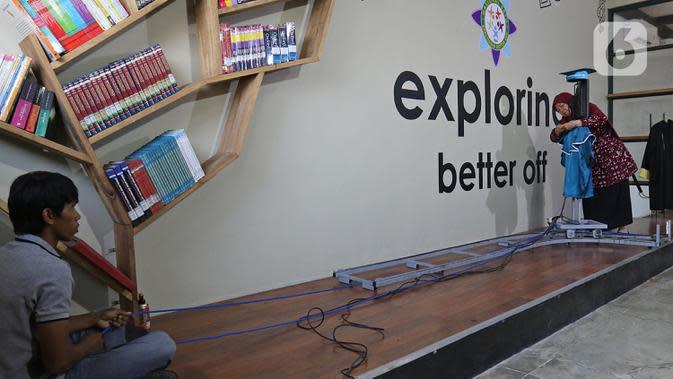 Operator mengoperasikan roboda (robot wisuda) saat wisuda virtual siswa Kelompok Bermain Taman Kanak-kanak (KB TK) Sekolah Nasional Satu di Bekasi, Rabu (1/07/2020). Sekolah itu menggunakan teknologi virtual dan roboda guna memudahkan prosesi wisuda di tengah Covid-19. (Liputan6.com/Herman Zakharia)