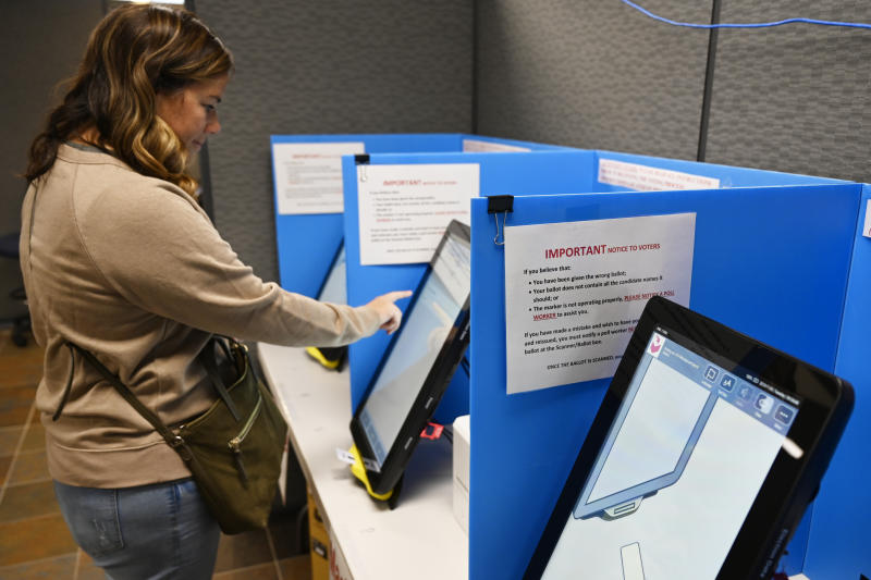 Courtney Parker votes on a new voting machine, Tuesday, Nov. 5, 2019, in Dallas, Ga. New voting machines that combine touchscreens with paper ballots are getting a limited test run in Georgia, as officials rush to meet a court-ordered deadline to retire the old system before any votes are cast in 2020. (AP Photo/Mike Stewart)