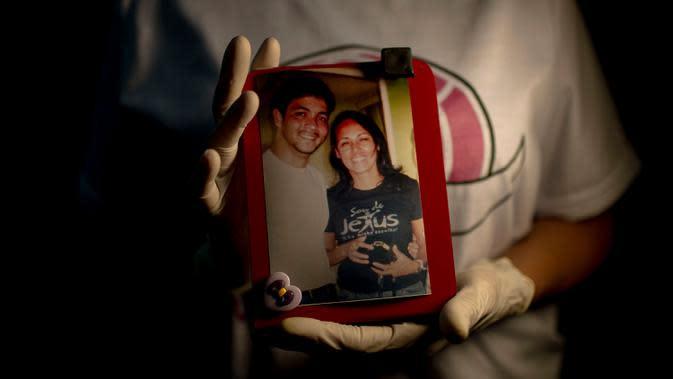 Regina Eleonora, 54, ibu dari mendiang perawat Alan Patrick - korban COVID-19 yang meninggal 22 April - memegang foto dengan putranya saat wawancara dengan AFP di Rio de Janeiro, Brasil, 25 Juni 2020. Sepertiga dari kematian global akibat COVID-19 terjadi di Amerika Latin. (Mauro Pimentel/AFP)
