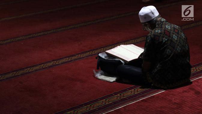 Umat muslim membaca Alquran saat malam takbiran di Masjid Istiqlal, Jakarta, Selasa (4/6/2019). Ratusan umat muslim berdatangan ke Masjid Istiqlal untuk merayakan malam takbir jelang melaksanakan salat Idul Fitri 1440 Hijriah. (Liputan6.com/Helmi Fithriansyah)