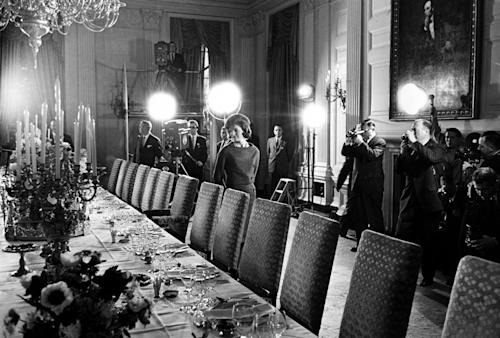 FILE - In this Jan. 15, 1962 file photo, U.S. first lady Jacqueline Kennedy, center, checks the table setting of the White House gold service in the state dining room as she conducts a tour of the newly-restored White House for television cameras in Washington to be aired the month afterwards. More than 80 million Americans tuned in. (AP Photo)