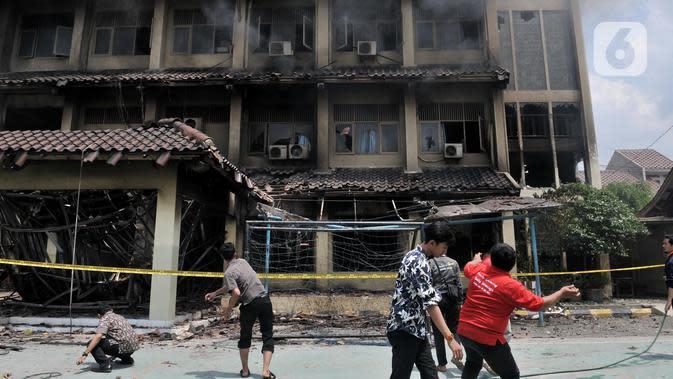 Sejumlah guru, pegawai, dan siswa mencoba memecahkan kaca dengan batu saat berusaha memadamkan api yang kembali muncul di Gedung SMK Yadika 6, Jatiwaringin, Pondok Gede, Kota Bekasi, Jawa Barat, Selasa (19/11/2019). Api muncul di salah satu ruang yang berada di lantai 2. (merdeka.com/Iqbal Nugroho)
