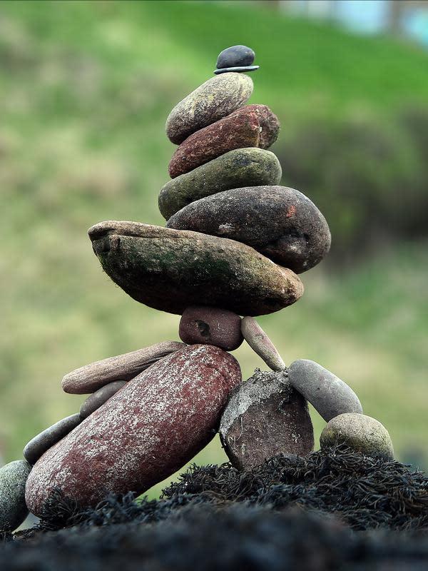 Salah satu wujud batu bertumpuk atau rock balancing dalam European Stone Stacking Championships 2018 di Dunbar, Skotlandia, Minggu (22/4). (ANDY BUCHANAN/AFP)