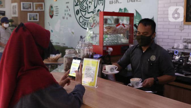 Nasabah memanfaatkan layanan digital bank melalui layanan Mandiri Syariah Mobile di Jakarta, Rabu (8/7/2020). Mandiri Syariah juga mengoptimalkan metode pembayaran digital tanpa uang tunai sebagai upaya untuk mengurangi risiko penyebaran Covid-19 di Era New Normal. (Liputan6.com/Angga Yuniar)