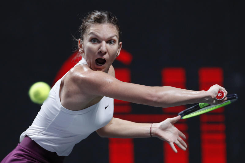 FILE - In this Oct. 28, 2019, file photo, Simona Halep, of Romani, eyes on the ball as she plays against Bianca Andreescu, of Canada, during their WTA Finals Tennis Tournament in Shenzhen, China's Guangdong province. Halep will be competing in the Australian Open tennis tournament, beginning Monday, Jan. 20, 2020. (AP Photo/Andy Wong, File)