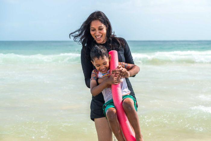 A woman plays with her son in the ocean.