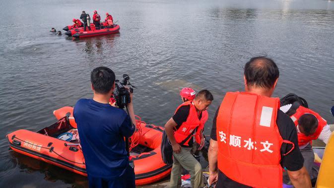 Tim penyelamat mencari korban selamat dari sebuah bus yang jatuh ke danau di Anshun, provinsi Guizhou, China, Selasa (7/7/2020). Sedikitnya 21 orang tewas usai bus yang membawa siswa untuk mengikuti ujian masuk perguruan tinggi atau gaokao itu menabrak pagar pembatas lalu tercebur ke danau (STR/AFP)