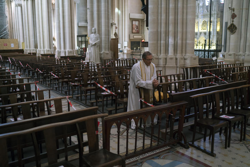 Priest Jean-Benoit de Beauchene prays in the empty St. Vincent de Paul church in Marseille, southern France, Sunday, March 22, 2020. As mass gatherings are forbidden due to measures to prevent the spread of COVID- 19, priests are using technology to reach worshippers forced to stay at home. For most people, the new coronavirus causes only mild or moderate symptoms. (AP Photo/Daniel Cole)