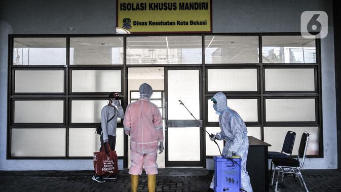 Petugas menyemprotkan disinfektan kepada tim medis dan pasien sebelum memasuki Pusat Rawat Isolasi Khusus Mandiri di Stadion Patriot Candrabhaga, Bekasi, Rabu (23/9/2020). Dinas Kesehatan Bekasi menyiapkan 57 tempat tidur di rumah sakit darurat itu untuk pasien Covid-19. (merdeka.com/Iqbal Nugroho)