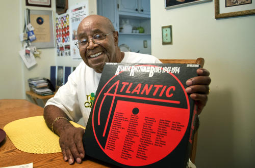 "Harold Winley, who performed ""Love Potion No. 9"" and other hits with the band The Clovers in the 50s, poses for photos Friday, Aug. 2, 2013 in Lauderdale Lakes, Fla. home, as he holds an old album cover. The 80-year-old says a splinter group is trying to keep him from performing using the band's name. (AP Photo/J Pat Carter)"