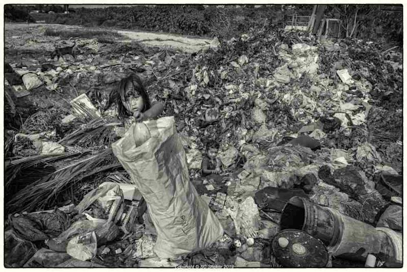 A child is seen scavenging through the landfill. ― Picture by SC Shekar