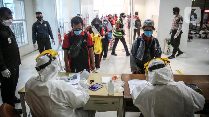 Sejumlah TKI Ilegal yang dipulangkan dari Malaysia mengantre untuk menjalani pemeriksaan kesehatan setibanya di Pelabuhan Tanjung Priok, Jakarta, Jumat (12/6/2020). Sebanyak 436 TKI Ilegal tersebut nantinya akan dipulangkan ke daerah asalnya di 22 provinsi. (Liputan6.com/Faizal Fanani)