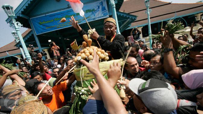 Warga memperebutkan sesaji gunungan pada acara Grebeg Syawal di halaman Masjid Agung Solo, Jawa Tengah, Jumat (8/7). Grebeg Syawal merupakan tradisi Keraton Kasunanan Surakarta untuk merayakan Idul Fitri. (Liputan6.com/Boy Harjanto)