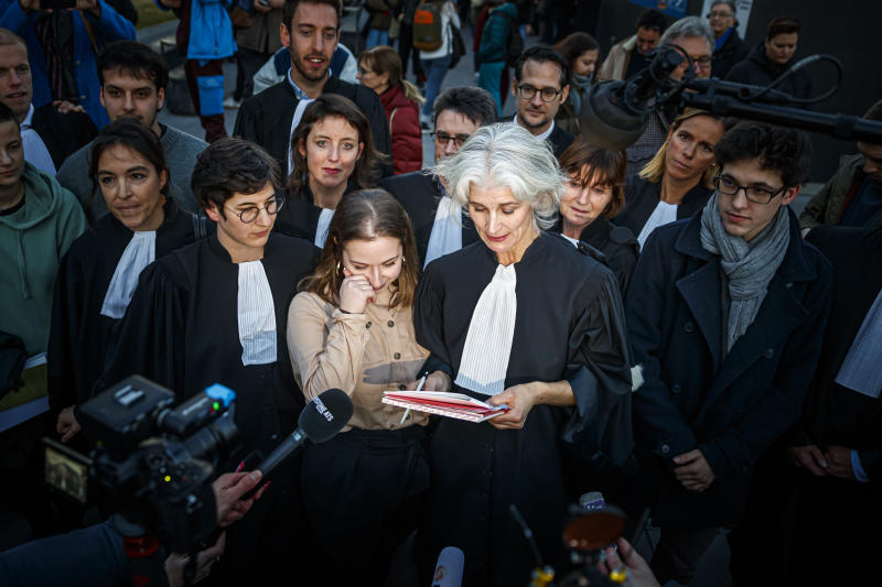 Defendant Dijana Simeunovic, center left, delivers a statement to the media, next to lawyer Irene Wettstein, center right, after the non-guilty verdict of the trial of 12 pro-climate activists of the LAC collective (Lausanne Action Climat), in front of the tribunal of Renens, Switzerland, Monday, Jan. 13, 2020.  A Swiss court on Monday threw out a case against a dozen climate activists who were on trial for storming a Credit Suisse office in Lausanne, Switzerland, and playing tennis inside — part of a protest against the bank's investments in fossil fuels that has ensnared its brand ambassador Roger Federer. (Valentin Flauraud/Keystone via AP)