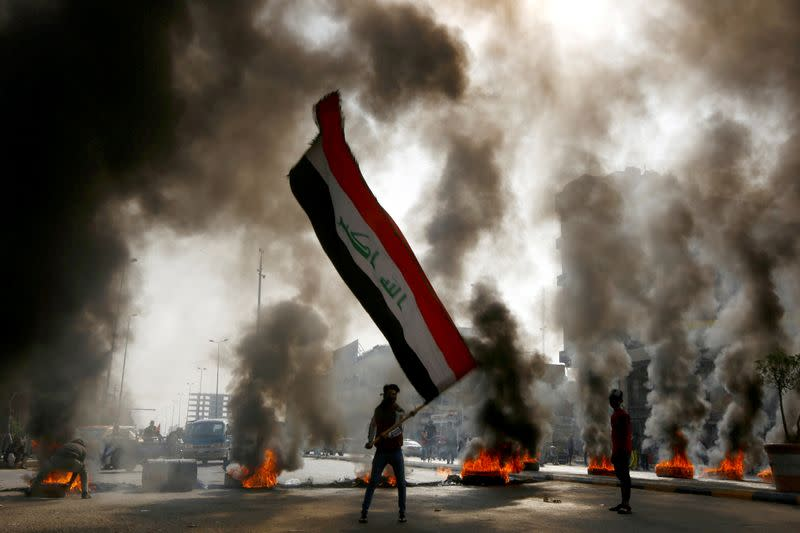 FILE PHOTO: A protester holds an Iraqi flag amid a cloud of smoke from burning tires during ongoing anti-government protests in Najaf