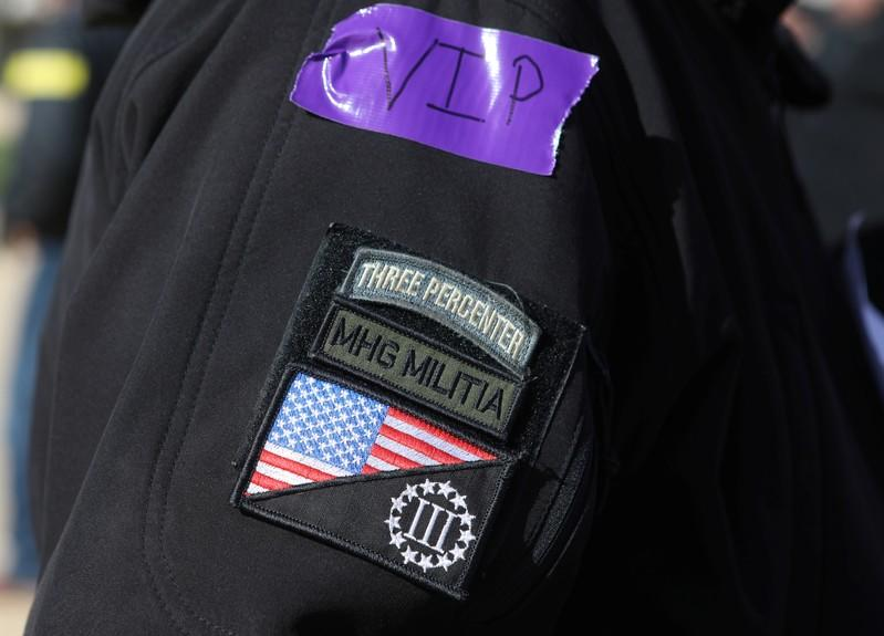 "Patches are seen on the sleeve of an attendee as militia members and pro-gun rights activists participate in the ""Declaration of Restoration"" rally in Washington, D.C."