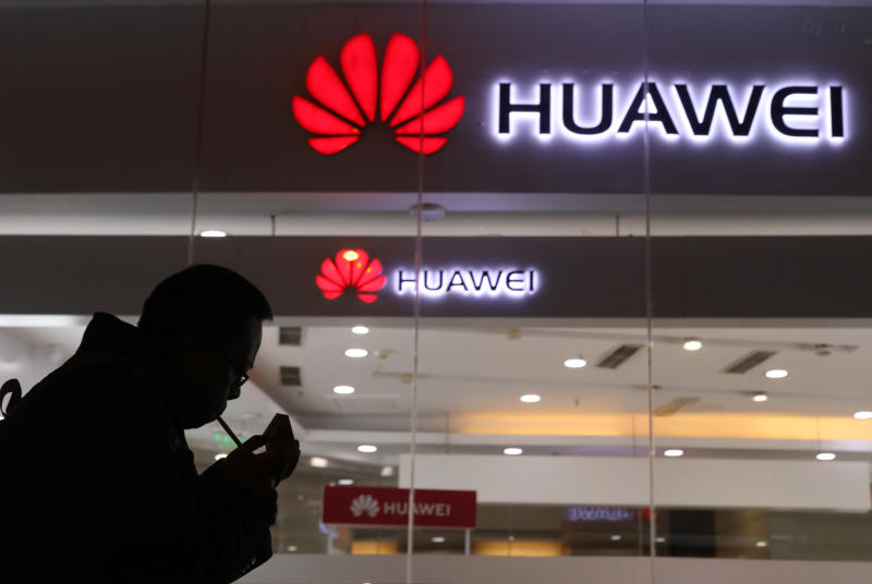FILE - In this Dec. 6, 2018, file photo, a man lights a cigarette outside a Huawei retail shop in Beijing.  The Federal Communications Commission on Friday, Nov. 22, 2019 voted, 5-0, to bar U.S. telecommunications providers from using government subsidies to pay for networking equipment from companies that are a threat to national security. The agency says China's Huawei and ZTE pose such a threat.