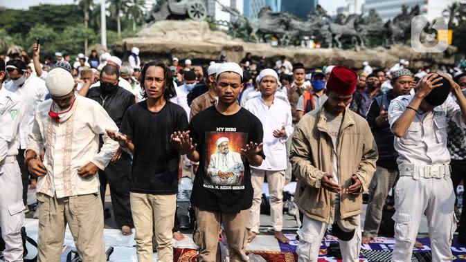 Massa aksi melaksanakan salat Ashar di sela unjuk rasa di Kawasan Patung Kuda, Jakarta, Selasa (13/10/2020). Massa aksi menolak Undang-Undang Cipta Kerja Omnibus Law tersebut salat beralaskan spanduk, kardus, hingga sajadah. (Liputan6.com/Faizal Fanani)