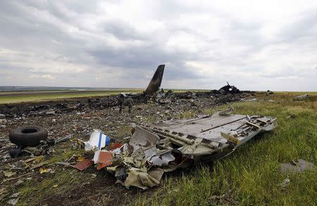 Pro-Russian separatists gather ammunition at the site of the crash of the Il-76 Ukrainian army transport plane in Luhansk, June 14, 2014. REUTERS/Shamil Zhumatov
