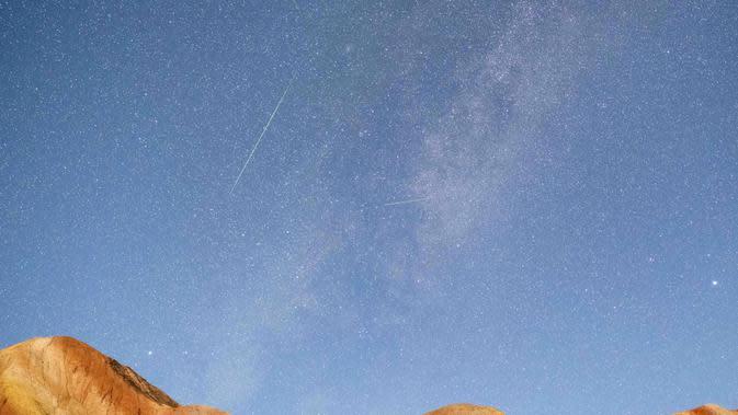 Foto eksposur panjang yang diabadikan pada 13 Agustus 2020 ini menunjukkan hujan meteor Perseid di Taman Geologi Nasional Danxia Zhangye di Zhangye, Provinsi Gansu, China barat laut. (Xinhua/Zhong Xiaoliang)