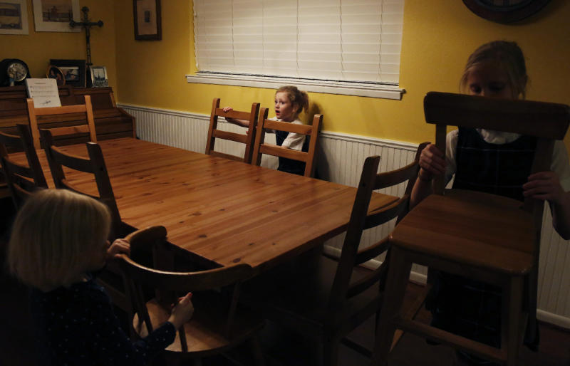 In this Feb. 7, 2020, photo, sisters, from left, Bernadette Whitfield, 4, Zoe-Catherine, 5, and Maggie, 9, choose seats around the dinner table at their home in north Dallas. (AP Photo/Jessie Wardarski)