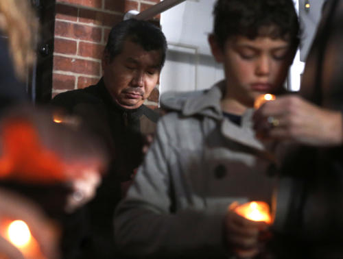 Chef Bill Kim stands behind other friends of Chicago Chef Charlie Trotter during a candlelight memorial for Trotter outside Trotter's former restaurant Tuesday, Nov. 5, 2013, in Chicago. Trotter, 54, died Tuesday, a year after closing his namesake Chicago restaurant that was credited with putting his city at the vanguard of the food world and training dozens of the nation's top chefs, including Grant Achatz and Graham Elliot. (AP Photo/Charles Rex Arbogast)