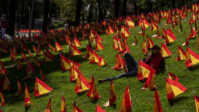 Seorang pria duduk di antara bendera Spanyol untuk mengenang korban COVID-19 di Madrid, Minggu (27/9/2020). Asosiasi keluarga korban virus corona memasang 53.000 bendera kecil Spanyol di sebuah taman Madrid untuk menghormati mereka yang meninggal akibat pandemi. (AP Photo/Manu Fernandez)