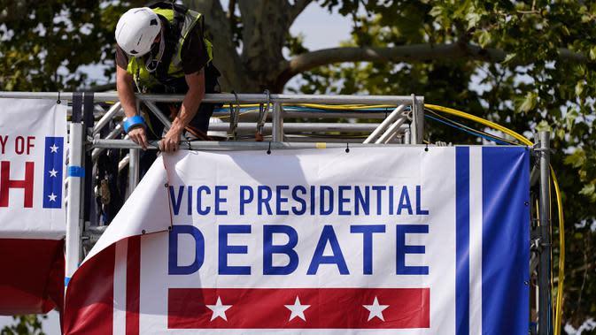 Pekerja memasang spanduk saat persiapan lanjutan untuk debat calon wakil presiden AS di luar Kingsbury Hall, Universitas Utah di Salt Lake City, Senin (5/10/2020). Debat cawapres petahana Mike Pence dan Senator California Kamala Harris akan digelar pada 7 Oktober. (AP Photo/Patrick Semansky)