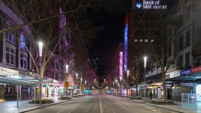 Jalan Swanston yang kosong pada malam hari di kawasan pusat bisnis Melbourne selama lockdown, Rabu (5/8/2020). Negara bagian Victoria, hotspot COVID-19 di Australia, melakukan lockdown dan menutup bisnis ritel sebagai upaya mengekang penyebaran virus corona. (AP Photo/Asanka Brendon Ratnayake)