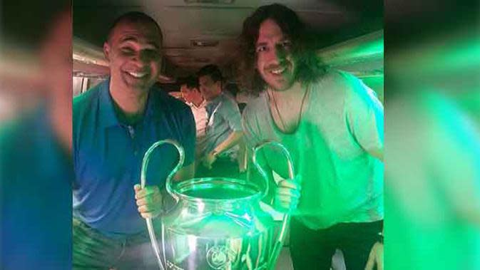 Ruud Gullit dan Puyol membawa trofi Liga Champions untuk fans sepakbola.