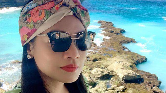 Pakai kacamata hitam serta ditambah dengan hiasan kepala, momen liburan Titi kamal semakin membuatnya bak remaja. (Liputan6.com/IG/@titi_kamall)