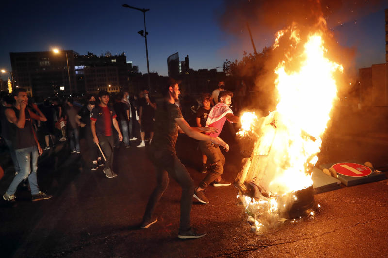 Anti-government protesters burn barriers to block a road during a protest against the political leadership they blame for the economic and financial crisis, in front of the government house in downtown Beirut, Lebanon, Thursday, June 11, 2020. (AP Photo / Hussein Malla)