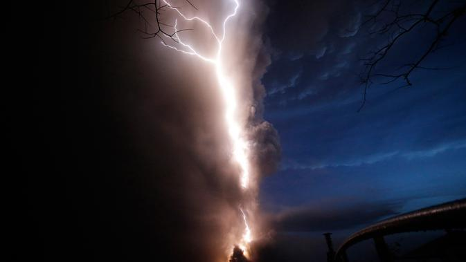 Petir menyambar saat Gunung Api Taal erupsi di Tagaytay, Provinsi Cavite, Filipina, Minggu (12/1/2020). Kantor bencana setempat telah mengevakuasi lebih dari 2.000 penduduk yang tinggal di pulau vulkanik tengah danau di dekat gunung tersebut. (AP Photo/Aaron Favila)