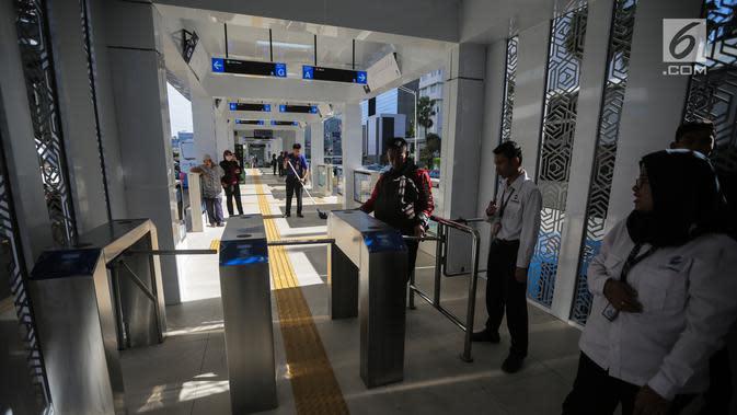 Penumpang melakukan tapping e-ticketing di gate in Halte Bus Transjakarta Bundaran Hotel Indonesia (HI), Jakarta, Senin (25/3). Halte Bundaran HI menjadi halte Transjakarta pertama yang terintegrasi fisik secara langsung dengan stasiun Moda Raya Terpadu (MRT). (Liputan6.com/Faizal Fanani)