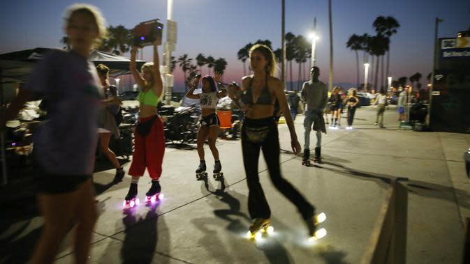 Orang-orang bermain sepatu roda di sepanjang trotoar Venice Beach di Venice, California, Kamis (3/9/2020). Menurut data Google, pencarian terkait sepatu roda dari Maret hingga Mei di Amerika Serikat meningkat hampir empat kali lipat. (Mario Tama/Getty Images/AFP)