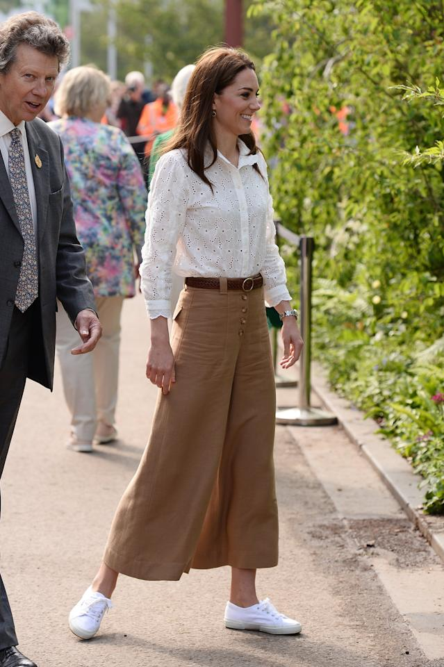 """<p>The duchess wore wide-legged pants with a white button-down and white Sugerga sneakers to visit the <a href=""""https://www.popsugar.com/fashion/Kate-Middleton-Wears-Wide-Leg-Pants-Chelsea-Flower-Show-46176642"""" class=""""ga-track"""" data-ga-category=""""Related"""" data-ga-label=""""https://www.popsugar.com/fashion/Kate-Middleton-Wears-Wide-Leg-Pants-Chelsea-Flower-Show-46176642"""" data-ga-action=""""In-Line Links"""">garden she helped design</a> at the Chelsea Flower Show.</p>"""