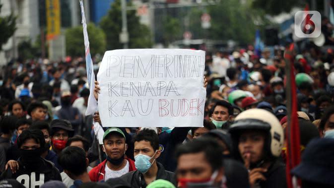 Pengunjuk rasa mengangkat poster saat berdemonstrasi menolak UU Cipta Kerja di kawasan Harmoni, Jakarta, Kamis (8/10/2020). UU Cipta Kerja yang disahkan beberapa waktu lalu memicu demonstasi sejumlah kalangan. (Liputan6.com/Faizal Fanani)