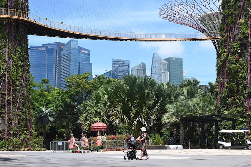 A woman pushes a baby stroller below Supertree Grove skyway at Gardens by the Bay in Singapore on September 9, 2020, after the popular tourist attraction was reopened to the public on September 7 following closures due to restrictions to halt the spread of the COVID-19 coronavirus. (Photo by ROSLAN RAHMAN / AFP) (Photo by ROSLAN RAHMAN/AFP via Getty Images)