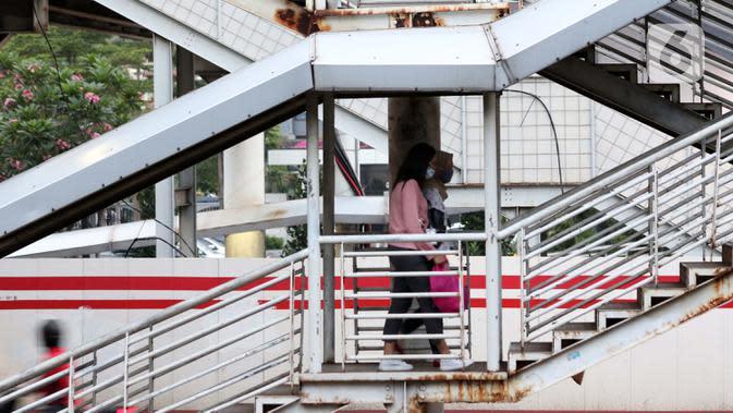 Warga berjalan di salah satu JPO di kawasan Jalan HR Rasuna Said, Jakarta, Rabu (8/7/2020). Wabah Covid-19 memengaruhi kondisi kesejahteraan masyarakat dan pertumbuhan ekonomi Indonesia pada tahun 2020 yang diproyeksikan -0,4 sampai dengan 1,0 persen. (Liputan6.com/Helmi Fithriansyah)