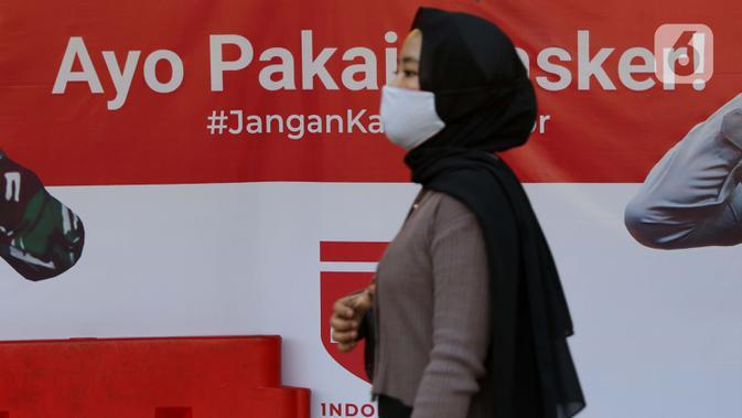 Warga melintasi spanduk sosialisasi Gerakan Ayo Pakai Masker di area pedestrian Stasiun Terpadu Tanah Abang, Jakarta, Kamis (27/8/2020). Guna menekan penyebaran Covid-19, Polda Metro Jaya dan Kodam Jaya terus mengampanyekan pentingnya menaati protokol kesehatan. (Liputan6.com/Helmi Fithriansyah)