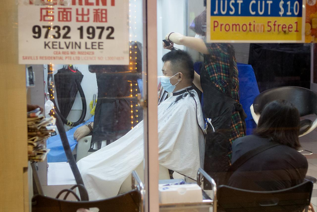 A man seen getting a haircut at a salon in Chinatown on 12 May 2020. (PHOTO: Dhany Osman / Yahoo News Singapore)