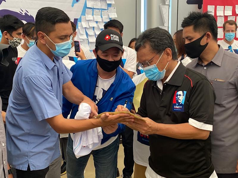 Shafie Apdal (second right) signs autographs for some of his supporters. — Picture courtesy of Sabah Chief Minister's Department