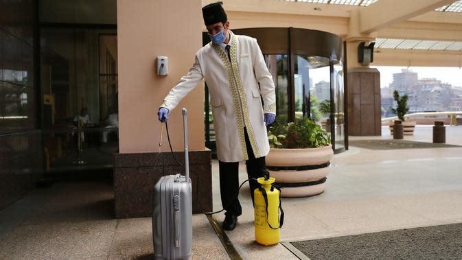 Seorang karyawan hotel mendisinfeksi sebuah koper di Hotel Conrad di Kairo, Mesir pada Selasa (2/6/2020). Pemerintah Mesir mulai mengizinkan puluhan hotel beroperasi kembali untuk melayani wisatawan lokal dengan kapasitas dibatasi 50 persen. (Xinhua/Ahmed Gomaa)